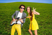 Young couple playing on guitar and enjoying the music, they shou — Stock Photo