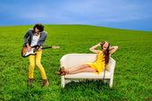 Uomo che suona un assolo della chitarra con ragazza sdraiata sul divano un — Foto Stock