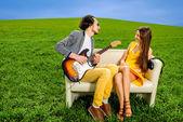 Hombre tocando bella canción a la chica guste en el sofá — Foto de Stock
