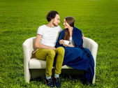 Young loving couple sitting on the couch on the green field — Stok fotoğraf