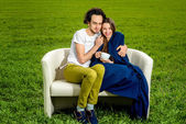 Young loving couple sitting on the couch on the green field — Photo