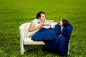 Man take care about his girlfriend on the couch on the green fie — Foto Stock