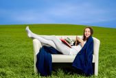 Girl reading book and drinking coffee on the couch in the green  — Stock Photo