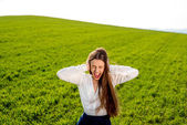 Lonely girl crying in the green field with cloudy sky — 图库照片