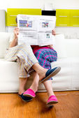 Married couple reading newspaper dressed in pajamas sitting in s — Stock Photo