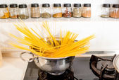 Long spaghetti cooking on the gas stove — Stockfoto