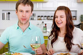 Funny couple eating macaroni at the kitchen with wine and salad — Stock Photo