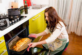 Married smiling couple putting apple to the oven at the kitchen — Stock Photo