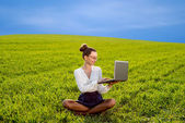 Young woman, girl working with laptop in green field, park with — Stock Photo