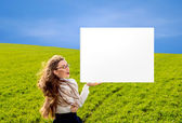 Businesswoman holding a message board on the green field with bl — Stock Photo