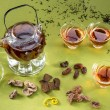Transparent teapot and glasses with tea and oriental sweets on — Stock Photo