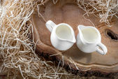 Sour cream in the white jugs on wooden desk with hay, up view — Stock Photo