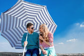Funny and young couple have fun with beach umbrella on the roof — Stock Photo