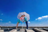 Young and pretty couple kissing on the roof under the umbrella o — Stock Photo