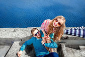 Smiling couple sitting on the pier embracing and smiling on the  — Stok fotoğraf