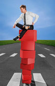 Successful business man on the top of pyramid made of red boxes — Stockfoto