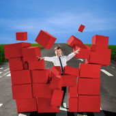 Business man breaking the wall of carton red boxes on the road — Stock Photo