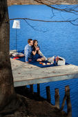 Couple sitting on terrace near the water — Stock Photo