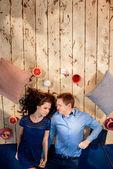 Paar auf Holzboden liegend mit Kissen und Süßigkeiten — Stockfoto