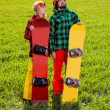 Couple in sport wear with snowboards standing on the grass and w — Stock Photo