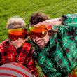Couple in ski suit and sun glasses have a funny look to the came — Stock Photo