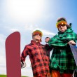Cool couple with snowboards in sport wear standing on the grass — Stock Photo