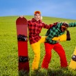 Couple in ski suit having fun with snowboards on the grass in gr — Stock Photo