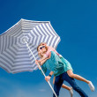 Girl having piggy back ride on a man with beach umbrella on blue — Stock Photo #45084585