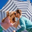 Young couple kissing under the umbrella on the blue sky — Stock Photo