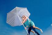 Girl having piggy back ride on a man with beach umbrella on blue — Stock Photo
