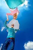 若いカップルが手を繋いでいるビーチ umbre で見下ろしています。 — ストック写真