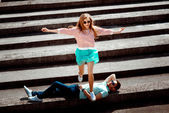 Smiling girl jumping over the man on the gray roof of apartment — Stock Photo