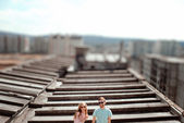 Young couple having fun on the gray roof of apartment building i — Stock Photo