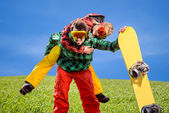 Man in ski suits giving piggyback ride to girlfriend with snowbo — Stock Photo