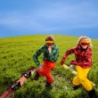 Couple having fun in ski suits with snowboards on the grass — Stock Photo