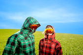 Couple in the ski suits standing in the green field — Stockfoto