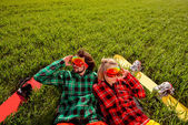 Couple in sportswear with snowboards lying on the grass — Stockfoto
