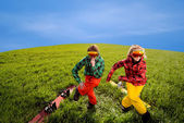 Couple having fun in ski suits with snowboards on the grass — Stok fotoğraf