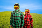 Couple in the ski suits standing in the green field — Stok fotoğraf