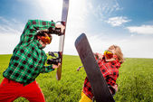 Young couple in ski suit have fun battle with snowboards togethe — Stok fotoğraf