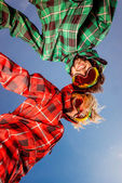 Couple in ski suits with sunglasses holding hands on blue sky ba — Stock Photo