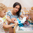 Little girl with mother choosing clothes in room — Stock Photo #33519811