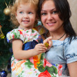 Mother and her little daughter by Christmas tree — Stockfoto