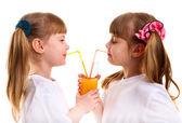 Little girls-twins drink orange juice — Stock Photo