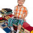 Stock Photo: Little boy on a pile of books