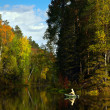 Fisher in boat is on the forest lake in autumn — Stock Photo