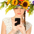 Beautiful girl with hat of flowers and phone in her hands — Stock Photo