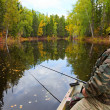 The fisher in boat is on the forest lake in autumn. — Stock Photo
