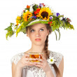 Stock Photo: Beautiful girl in hat of flowers and cup of tea