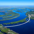 Aerial view flooded forest plains and road crossing it — Stock Photo